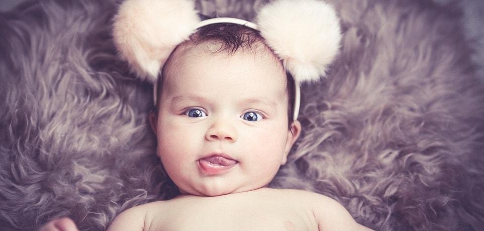 Bebé con cinta de pompones